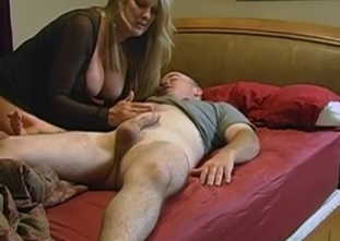 Skillful busty mommy jerks off her son dick